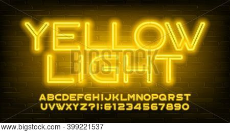 Yellow Light Alphabet Font. Neon Light Letters And Numbers. Brick Wall Background. Stock Vector Type