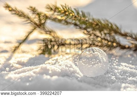 Frozen Bubble With Ice Crystals On Snow With Fir Branch At Sunset. Christmas Background