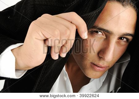 Portrait of a serious young man making headscarf with his jacket