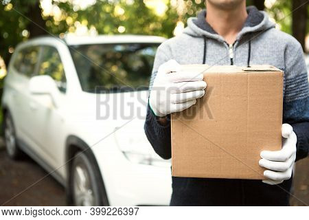A Cardboard Box With Space For Text In The Hands Of A Male Courier In White Gloves. Courier On The B
