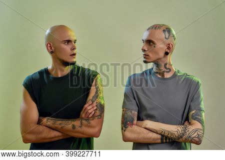 Horizontal Shot Of Two Young Caucasian Twin Brothers With Tattoos And Piercings Keeping Arms Crossed