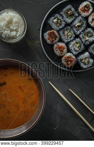 A Bowl Of Tom Yam Soup, A Jar Of Rice And A Set Of Sushi. Top