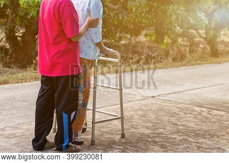 Asian Old Woman Standing With Her Hands On A Walker With Daughter's Hand,hand Of Old Woman Holding A
