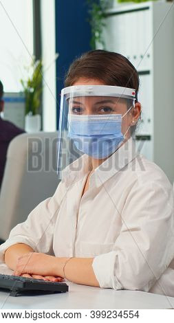 Manager Woman With Visor And Protection Mask Looking At Camera Smiling In New Normal Business Office