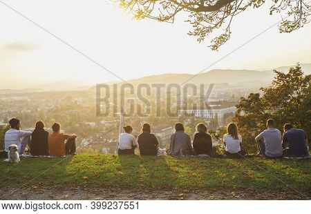 Ljubljana, Slovenia, October 2020: People Sit On The Mountain And Admire The Sunset Over The Autumn