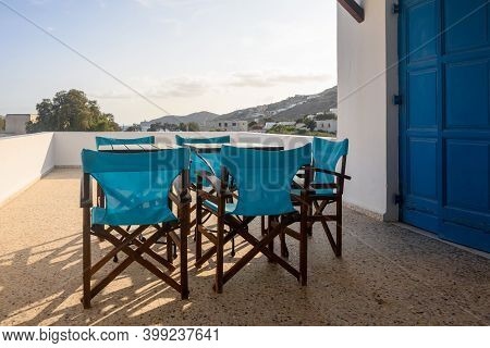 Ios, Greece - September 20, 2020: Chairs With Tables On The Balcony Of Greek Summer Villa On Ios Isl