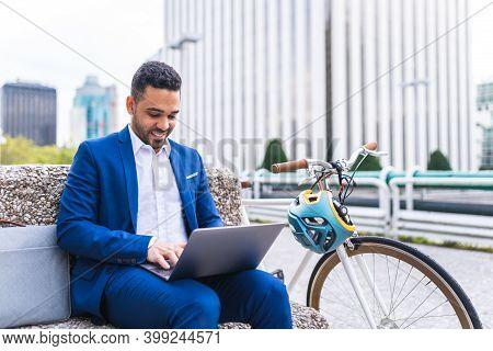 Latino Businessman Using Laptop Outdoors .