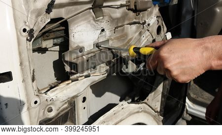 The Hand Of A Car Workshop Worker With A Yellow Screwdriver Unwinding The Fasteners Of The Window Re