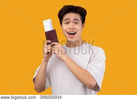Cheap Flights Concept. Portrait Of Surprised Excited Asian Man Holding Passport And Boarding Pass Ti
