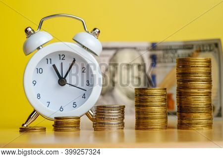 Stacks Of Coins In Row Ascending And Alarm Clock With 100 Dollars Banknote On Background. Time Is Mo
