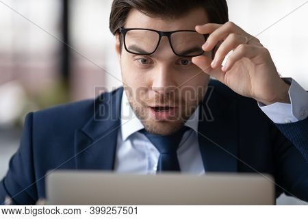 Close Up Shocked Businessman Taking Off Glasses, Reading Unexpected News