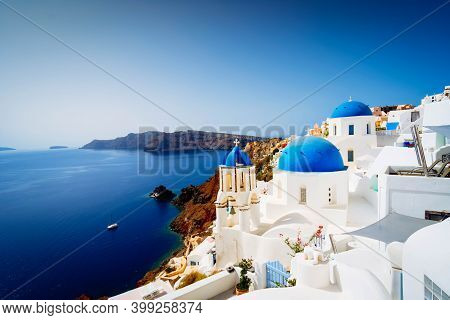 View Of Traditional Greek Village Oia Of Santorini, With Blue Domes Against Sea And Caldera, Greece,