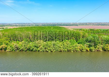 Aerial View Of Green Forest At Riverside . Flowing River And Nature Reserve