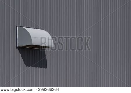 Side View Of Dryer Vent On Grey Corrugated Metal Factory Building Wall
