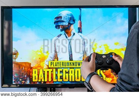 Woman Holding A Xbox Controller And Playing Popular Video Game Player Unknowns Battlegrounds Pubg On