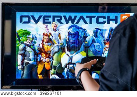 Woman Holding A Steam Controller And Playing Popular Video Game Overwatch On A Television And Pc