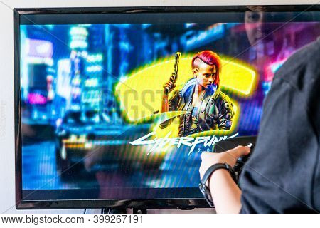 Woman Holding A Steam Controller And Playing Popular Video Game Cyberpunk 2077 On A Television And P
