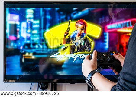 Woman Holding A Xbox Controller And Playing Popular Video Game Cyberpunk 2077 On A Television And Pc