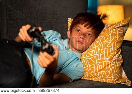 Alone Young Kid Playing Video Game Using Joystick During Late Night While Sleeping On Bed - Concept