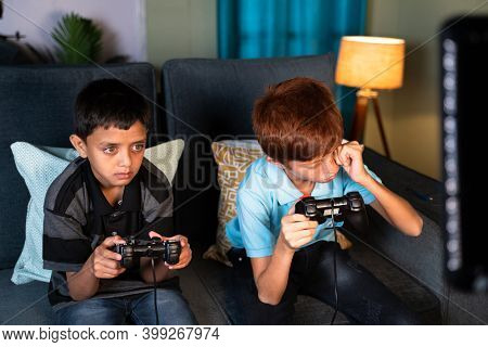 Concept Of Eye Strain Due To Over Night Video Game Play - Two Kids Playing Video Game During Late Ni
