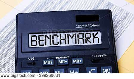 A Calculator Labeled Benchmark Is On The Table Near The Report. Financial Concept