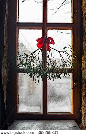 Branch Of Christmas Mistletoe With Red Bow On Window Background