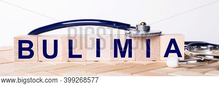 The Word Bulimia Is Written On Wooden Cubes Near A Stethoscope On A Wooden Background. Medical Conce