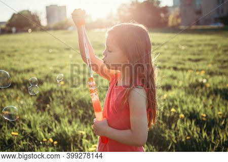 Preschool Caucasian Girl Blowing Soap Bubbles In Park On Summer Day. Child Having Fun Outdoor. Authe