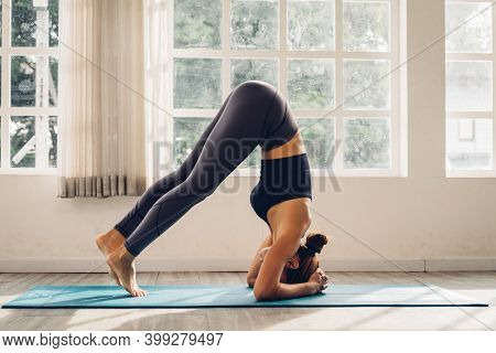 Asian Young Woman Training Yoga Doing Headstand Pose On Floor In Room In Morning. Instructor Woman L