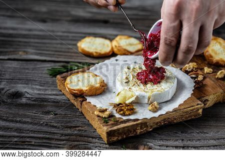 Traditional French Homemade Baked Camembert Cheese Cranberry Sauce Is Poured Over Cheese From A Jug.