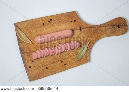 Sausages On A Wooden Board. A Chopped Sausage Next To A Whole Sausage. Meat Product On A White Backg