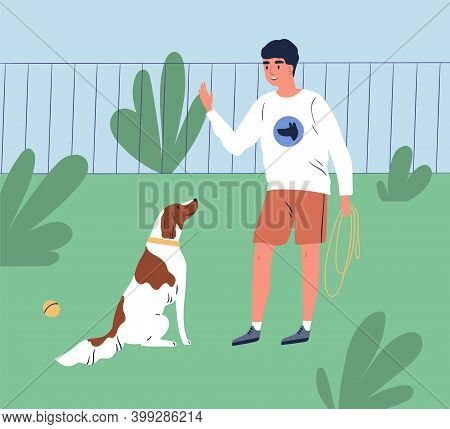 Male Owner Training His Dog To Command Sit. Trainer Teach Obedient Purebred Spaniel In Park. Cheerfu