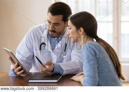 Male Doctor Explain Results On Tablet To Female Patient
