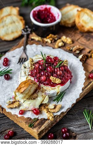 Traditional French Homemade Baked Camembert With Toasts, Rosemary, Cranberries And Nuts On Rustic Wo