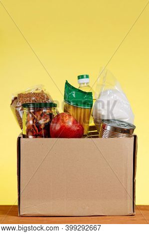 Food Donation Concept. Donation Box With Food For Donation On Yellow Backround. Assistance To The El