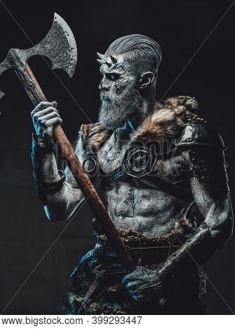 Northern Warrior Risen From The Dead With Pale Skin And Two Handed Axe In Armour With Fur In Dark Ba