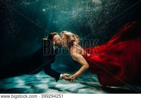 A Woman In A Red Dress And A Man In A Suit Are Kissing Underwater.a Pair Of Floats Under Water