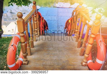 Entrance To The Boat Station With Life Jackets On The Railing. The Dock With Paddle Boats In Summer