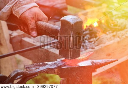 Blacksmith Hammer Hits The Hot Metal. Forging Of Iron Objects In A Retro Forge. The Process Of Worki