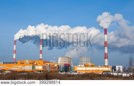 Factory Main Pipes That Emit A Lot Of Smoke Into The Atmosphere. The Blue Sky Is Obscured By Smoke F