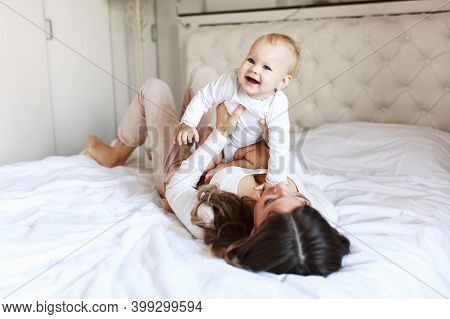 Young Mother Holding Her Newborn Child. Mom Nursing Baby. Woman And New Born Boy Relax. Nursery Inte