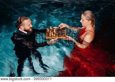 A Man In A Suit And A Girl In A Red Dress Play Chess On The Water In The Pool