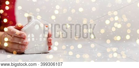 Womens Hands Hold New Small Ceramic House With Windows With Copy Space. Golden Lights Abstract Holid
