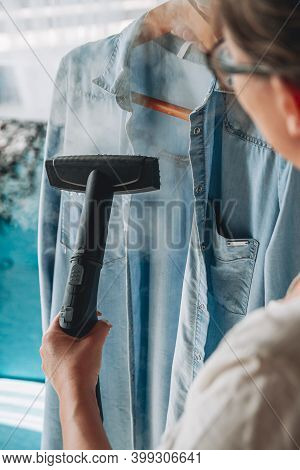 Woman Is Steaming Steam Cleaner Shirt In A Room At Home