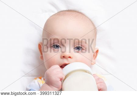 Caucasian Baby Boy With Baby Milk Bottle On White Blanket. Close Up. Baby Feeding And Artificial Nut