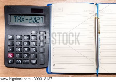 Tax Word And 2021 Number On Calculator. Business And Tax Concept. Pay Tax In 2021 Years.