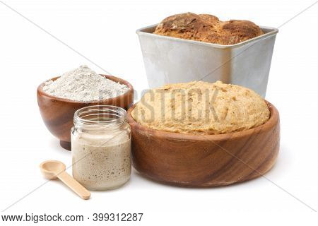 Natural Leaven For Bread In A Glass Jar, Wooden Bowl Of Dough, Bowl Of Flour And Freshly Baked Loaf
