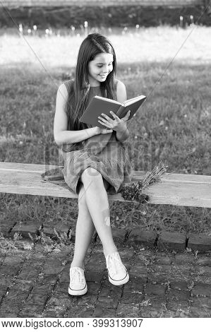 Reading Helps Your Seed Of Knowledge Grow. Little Child Read Book On Park Bench. Small Girl Enjoy Re