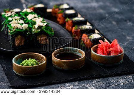 Sushi Rolls Set Served On Black Stone Slate On Dark Background, Set Of Japanese Sushi Rolls With Soy