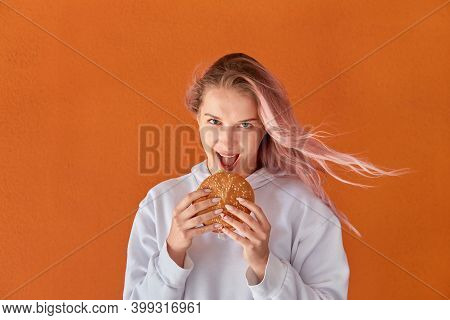 A Woman Eats A Big Delicious Burger And Looks At The Camera. Orange Background.